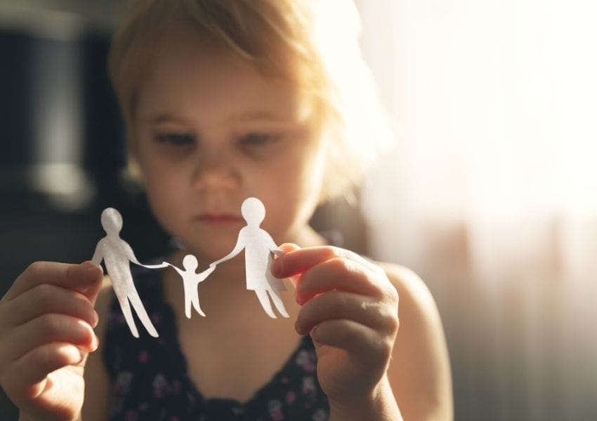 Child playing with paper cut out of family